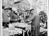 Żyd handlujący towarami na rynku głównym w Garwolinie. Na zdjęciu uchwyceni zostali również mieszkańcy Garwolina, którzy robią zakypy u Żyda, W tle kościół z wieżami przewojennymi. Zdjęcie wykonano w latach 30-tych. Ze zbiorów Aliny Janowskiej - aktorki