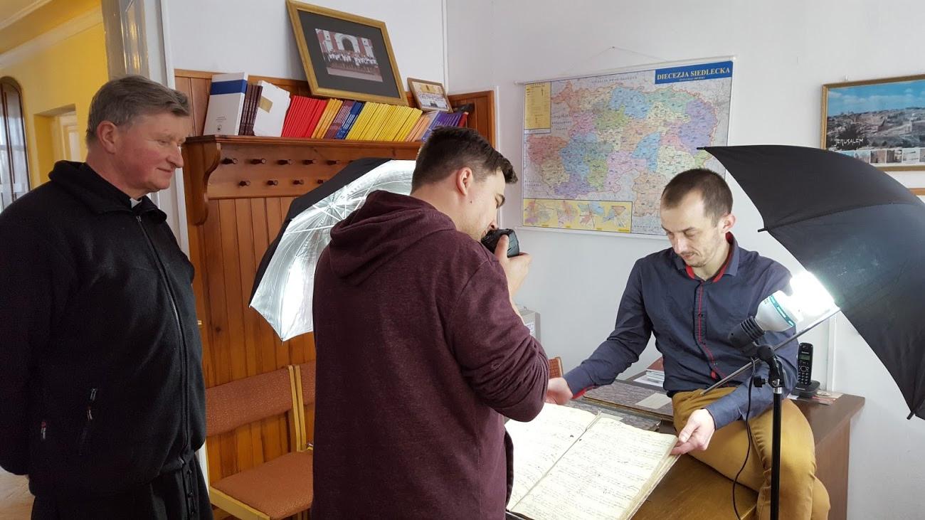 Fotografowanie ksiąg metrykalnych parafii Maciejowice pod czujnym okiem proboszcza Ks. Kan. Stanisława Marczuka