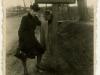 Kobieta przy tablicy informującej o wjeździe do miasta Garwolina - obstawiamy wjazd od strony Siedlec. Okres okupacji niemieckiej.